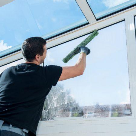 Fensterreinigung Mann reinigt Fenster